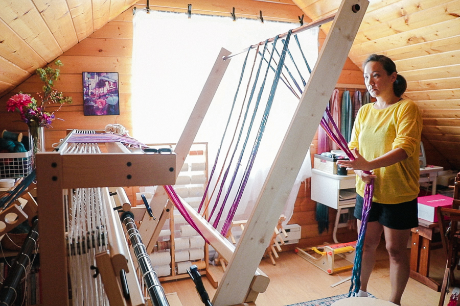 Felicia Lo using a warping trapeze to beam a warp on the Louet Spring Loom