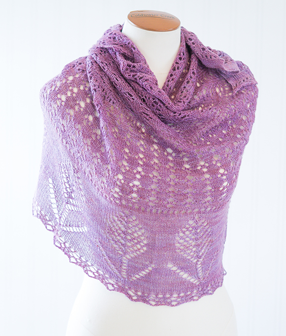 Evening Fields lace shawl knitting pattern featuring eyelets and flower motifs. Worked in CashSilk Lace weight yarn